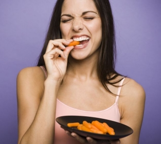 Woman eating carrot sticks