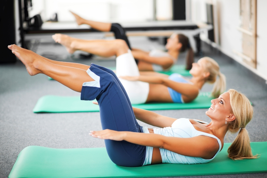 Group of women doing Pilates exercises.