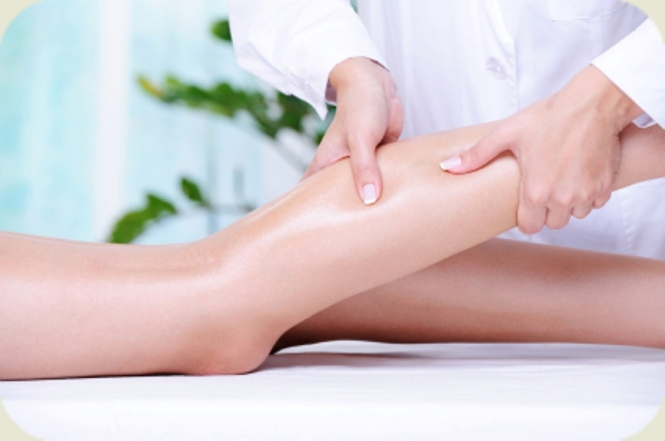 Therapeutic massage for the female beautiful leg by beautician in the spa salon