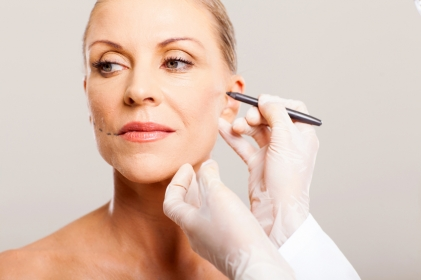 doctor drawing correcting lines on senior woman face before plastic surgery