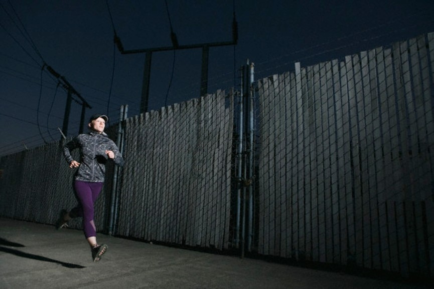 Woman Running Past Fence --- Image by © Scott Areman/Corbis